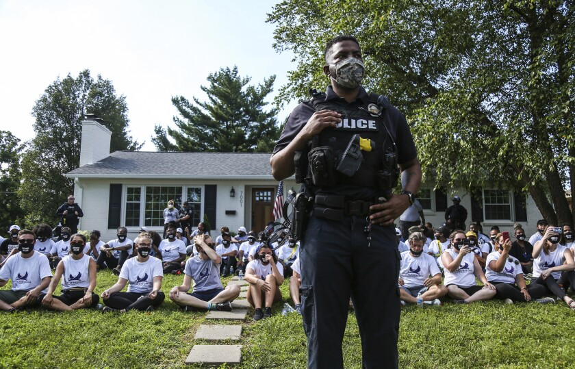 Officers keep watch as protesters sit outside the home of Kentucky Attorney General Daniel Cameron