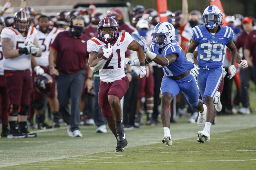 Virginia Tech running back Khalil Herbert (21) breaks free for a first-down run ahead of Duke safety Marquis Waters (0) and cornerback Jeremiah Lewis (39) during the second half of an NCAA college football game Saturday, Oct. 3, 2020, in Durham, N.C. (Nell Redmond/Pool Photo via AP)