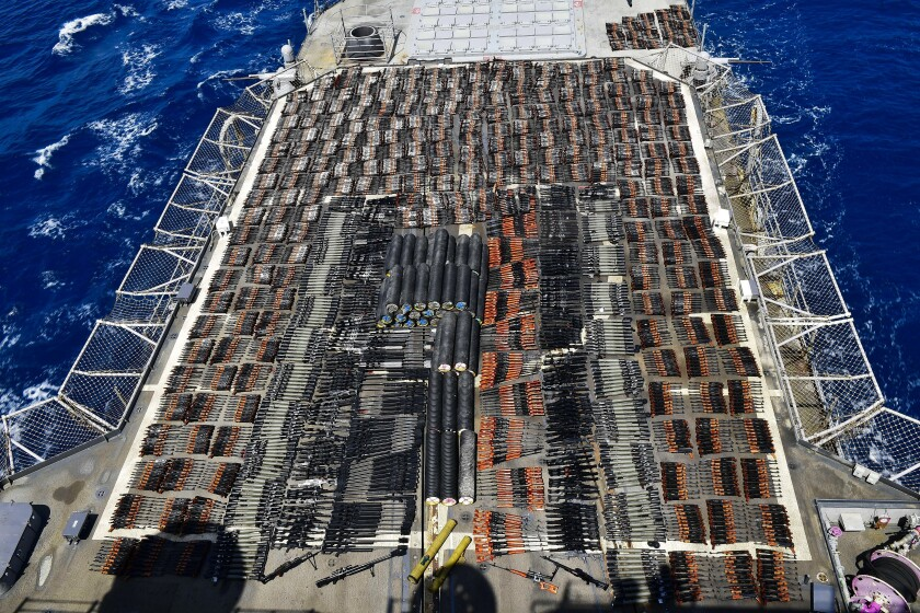Thousands of weapons laid out in rows on a ship deck