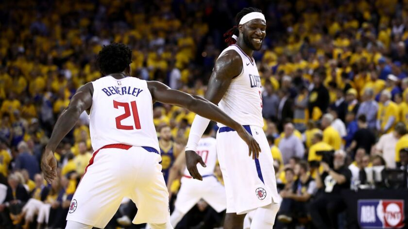 Clippers teammates Patrick Beverley, left, and Montrezl Harrell celebrate during a playoff game against the Golden State Warriors last season.