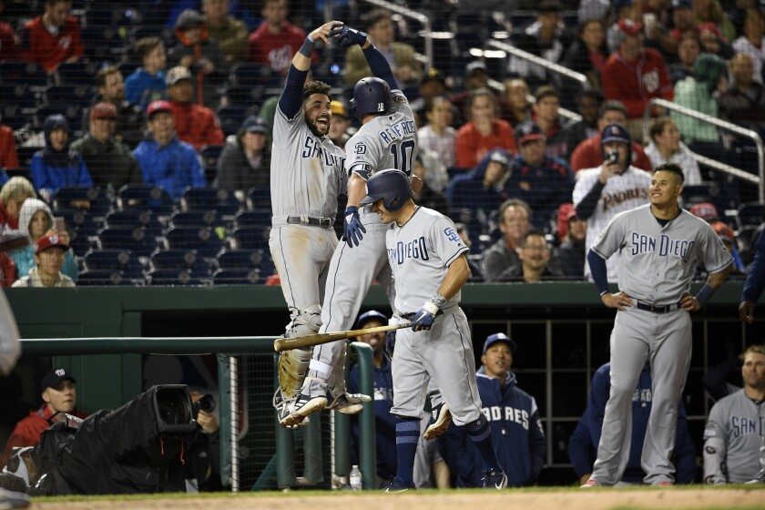 Hunter Renfroe (10) celebrates his home run with Austin Hedges (left) as Ian Kinsler (front) and Manny Machado look on during an April game against the Washington Nationals.