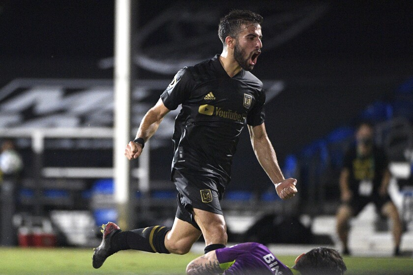 LAFC's Diego Rossi reacts after scoring past Galaxy goalie David Bingham, at bottom, in the second half July 18, 2020.