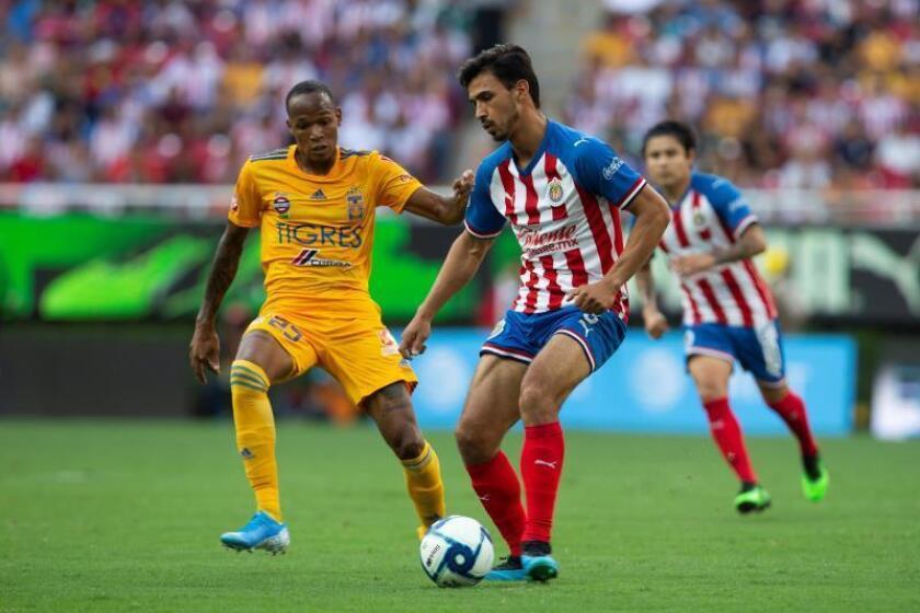 El jugador de Chivas Oswaldo Alanís (d) disputa el balón con Luis Quiñones (i) Tigres en el estadio Akron, en la ciudad de Guadalajara (México). EFE/ Francisco Guasco/Archivo