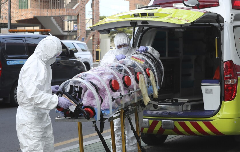 """Medial workers carry a patient infected with the coronavirus onto an ambulance at an elderly care facility in Ulsan, South Korea, Monday, Dec. 7, 2020. South Korea's health minister said Monday that the Seoul metropolitan area is now a """"COVID-19 war zone,"""" as the country reported another 615 new infections and the virus appeared to be spreading faster. (Kim Young-tae/Yonhap via AP)"""