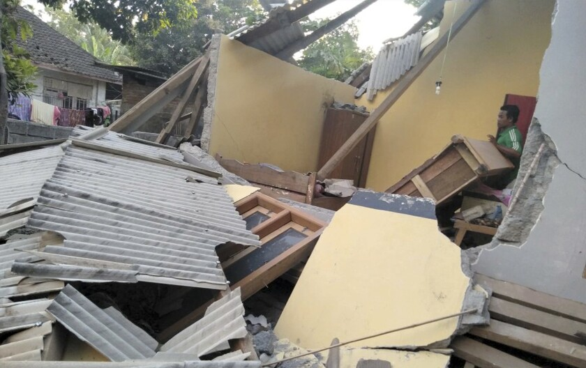 In this image made from video released by Indonesia's Disaster Mitigation Agency, a man inspects the damage caused by an early morning earthquake on the island of Lombok, Indonesia, Sunday, July 29, 2018.