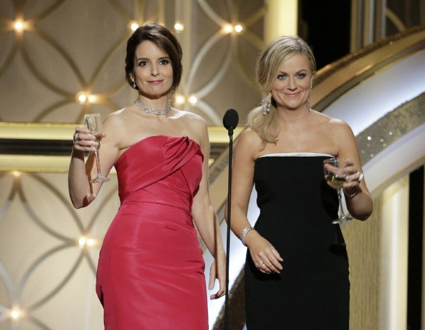 Tina Fey, left, and Amy Poehler will return to host next year's Golden Globe Awards.