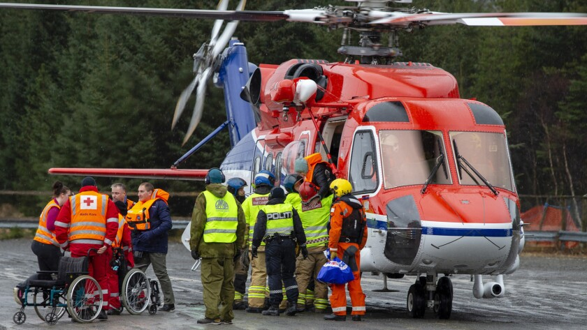 Passengers are helped from a rescue helicopter in Fraena, Norway, Sunday March 24, 2019, after being