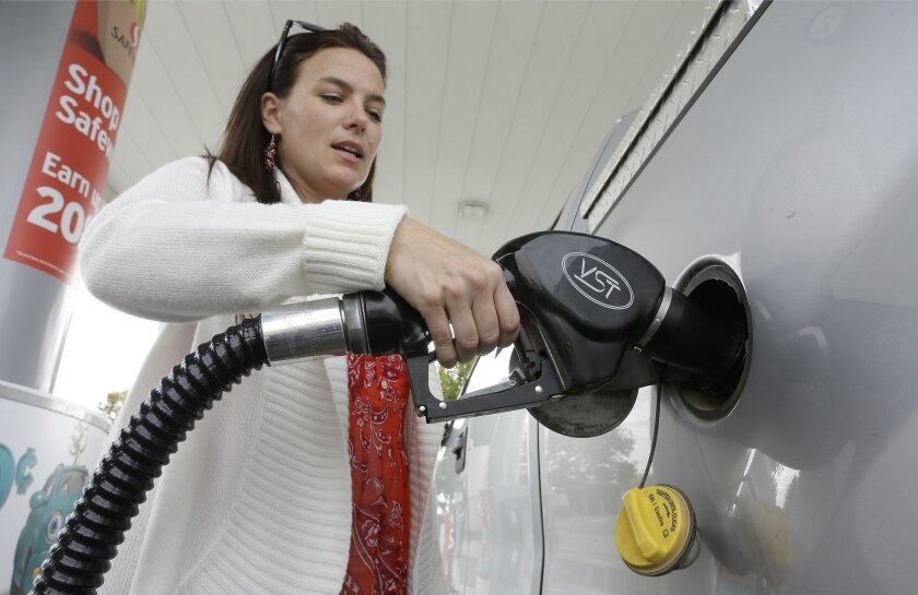 In this photo taken Nov. 12, 2014, Lydia Holland fills up at a gas station in Sacramento, Calif. The United States and China can look to California as an example of the costs and challenges of fighting global warming, since the state has imposed some of the world's toughest air quality standards as