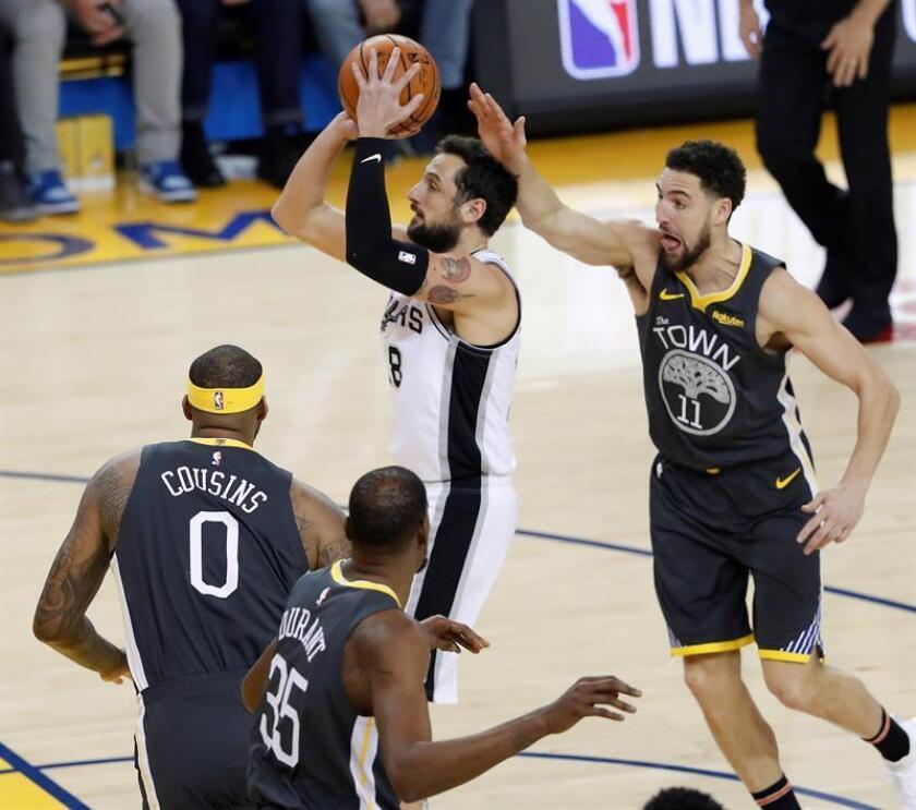 El escolta de los Spurs de San Antonio Marco Belinelli (c) lucha por el balón con el escolta de de los Warriors de Golde State Klay Thompson (d) durante el partido de la NBA que enfrentó, este miércoles 6, a los Spurs de San Antonio y los Warriors de Golden State en el Oracle Arena en Oakland, California (Estados Unidos). EFE