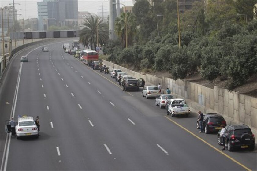 Israeli motorists stand still next to their cars on a freeway as a two-minute siren sounds in memory of victims of the Holocaust in Tel Aviv, Israel, Monday, April 8, 2013. Holocaust remembrance day is one of the most solemn on Israel's calendar with restaurants and places of entertainment shut dow