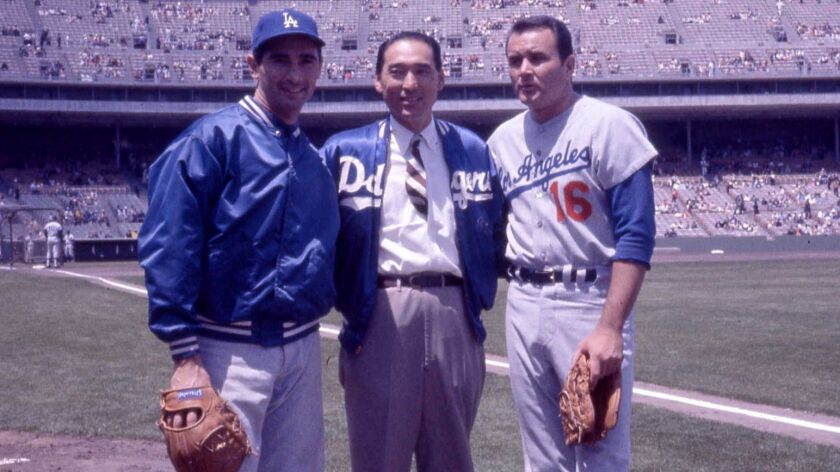 1964 photo of Dodgers pitcher, Sandy Koufax, left, clubhouse man, Nobe Kawano, center, and pitcher R