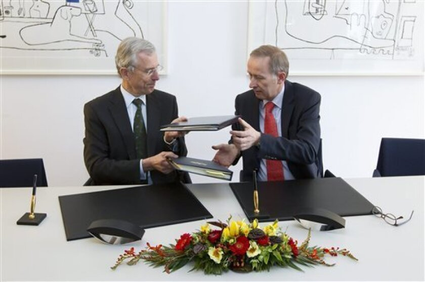 Peter Gottwald, German ambassador in Switzerland, left, and Michael Ambuehl, Switzerland's State Secretary for International Financial and Tax Matters, exchange their folders after the signing of an additional protocol on a tax agreement between Germany and Switzerland in Bern, Switzerland, Thursday, April 5, 2012. (AP Photo/Keystone/Peter Klaunzer)