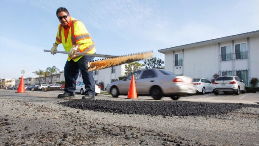 Jose Nuñez, who repairs potholes for the city of San Diego, works along Jewell Street in Pacific Beach.