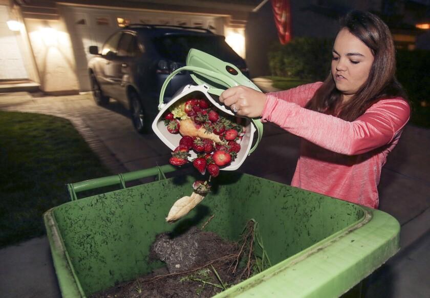 Oceanside resident Chelsee Brown deposited food scraps in the appropriate trash bin