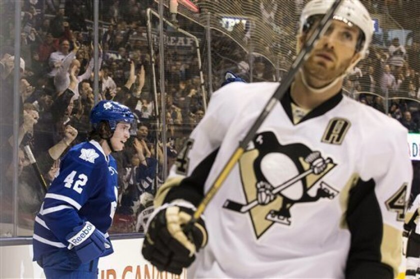 Toronto Maple Leafs' Tyler Bozak, left, celebrates scoring as Pittsburgh Penguins' Brooks Orpik skates by during the second period of their NHL hockey game, Thursday, March 14, 2013, in Toronto. (AP Photo/The Canadian Press, Chris Young)