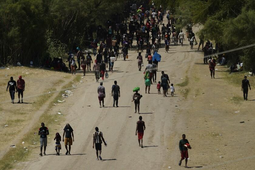 Migrantes haitianos caminan por un camino de tierra después de ingresar a Estados Unidos desde México