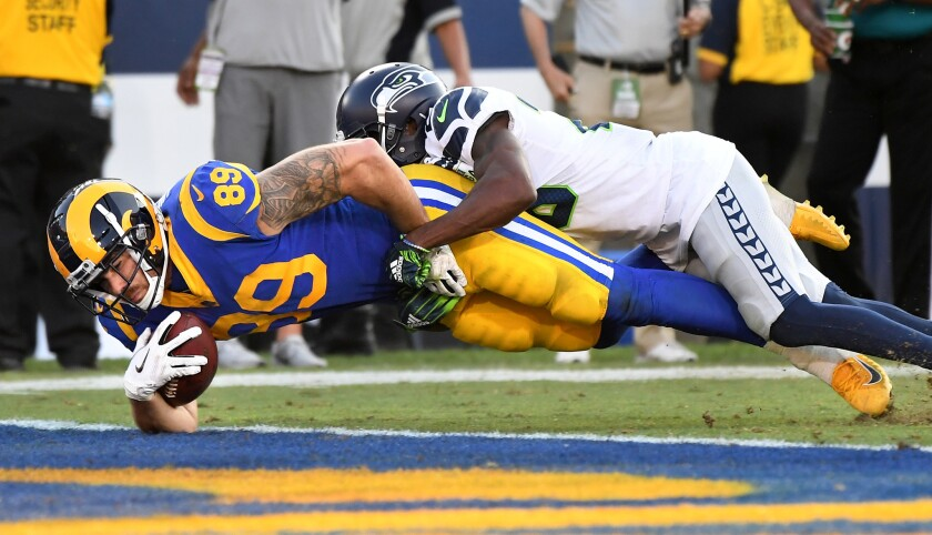 Rams tight end Tyler Higbee scores a touchdown against Seattle Seahawks cornerback Justin Coleman in the fourth quarter at the Coliseum on Sunday.