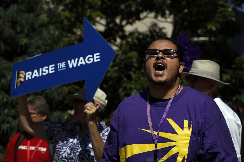 Armando Munoz, 31, of Los Angeles, joins a march in Long Beach in support of a $15 minimum wage.