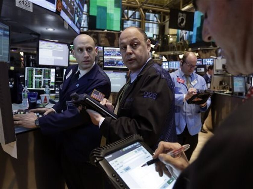 Specialist Meric Greenbaum, left, works with traders on the floor of the New York Stock Exchange Monday, April 29, 2013. World stock markets were mostly higher Tuesday April 30, 2013, brushing off tepid Japanese manufacturing data a day after the Standard & Poor's 500 index closed at another all-ti
