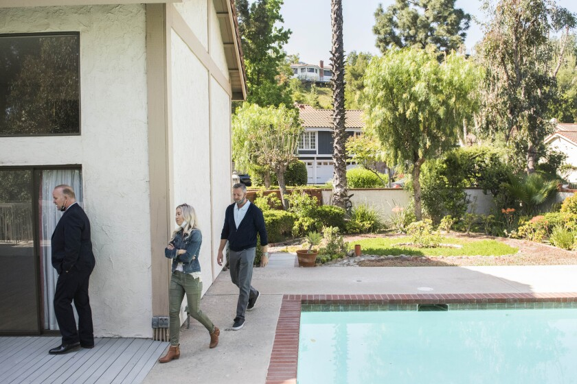 Real estate agent Derek Oie, left, shows a home to his clients Sarah and Vik Szemerei in North Tustin during their allotted 30 minute time slot on Saturday, April 17, 2021. ( Photo by Nick Agro / For The Times )