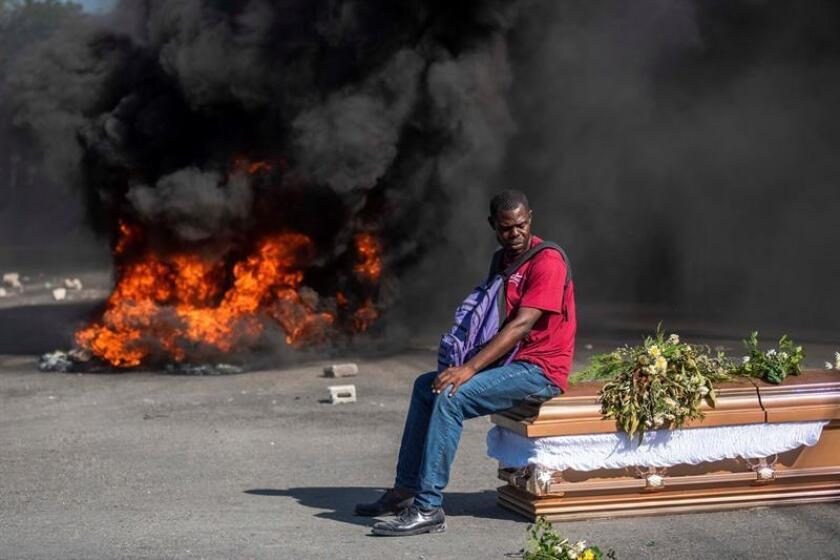 A man remains seated on the coffin of a person during a protest that occured while dozens of people accompanied four coffins to the cemetery in Port-au-Prince, Haiti, 04 March 2019. The opposition Democratic and Popular Sector of Haiti led the funeral of four people who died in mid-February in Port-au-Prince during violent protests calling for the resignation of the country's president, Jovenel Moise. Some 300 people advanced with the bodies to the cemetery when they tried to carry out protests that were repressed with tear gas by the Haitian National Police (PNH). Opponents of the Democratic and Popular Sector blame the government for the deaths and called for new demonstrations next Thursday. Haiti is going through a deep economic and political crisis, aggravated by the massive and v