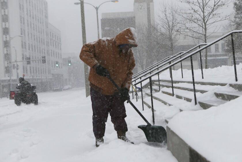 Roanoke, Va., city worker Larry White shovels the steps of City Hall.