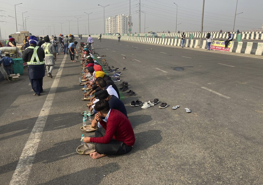 Protestors eat a meal on a highway during a strike in New Delhi, India, Tuesday, Dec. 8, 2020. Farmers in India are calling for a shutdown as their protest against new agriculture laws continue. Thousands of farmers are protesting reforms that they say could devastate crop prices and reduce their earnings. (AP Photo/Shonal Ganguly)