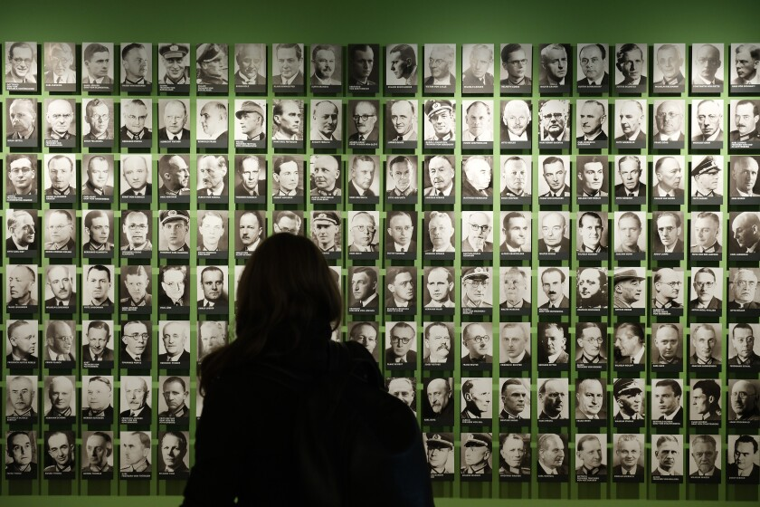 A visitor looks at portraits of members of the World War II German resistance July 8 at the German Resistance Memorial Center in Berlin. Claus von Stauffenberg is visible at bottom right,