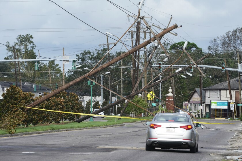 Traffic diverts around downed power lines and sideways power poles