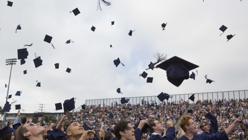 Recent Newport Harbor High School graduates celebrate by tossing their caps on Thursday, June 21, 20
