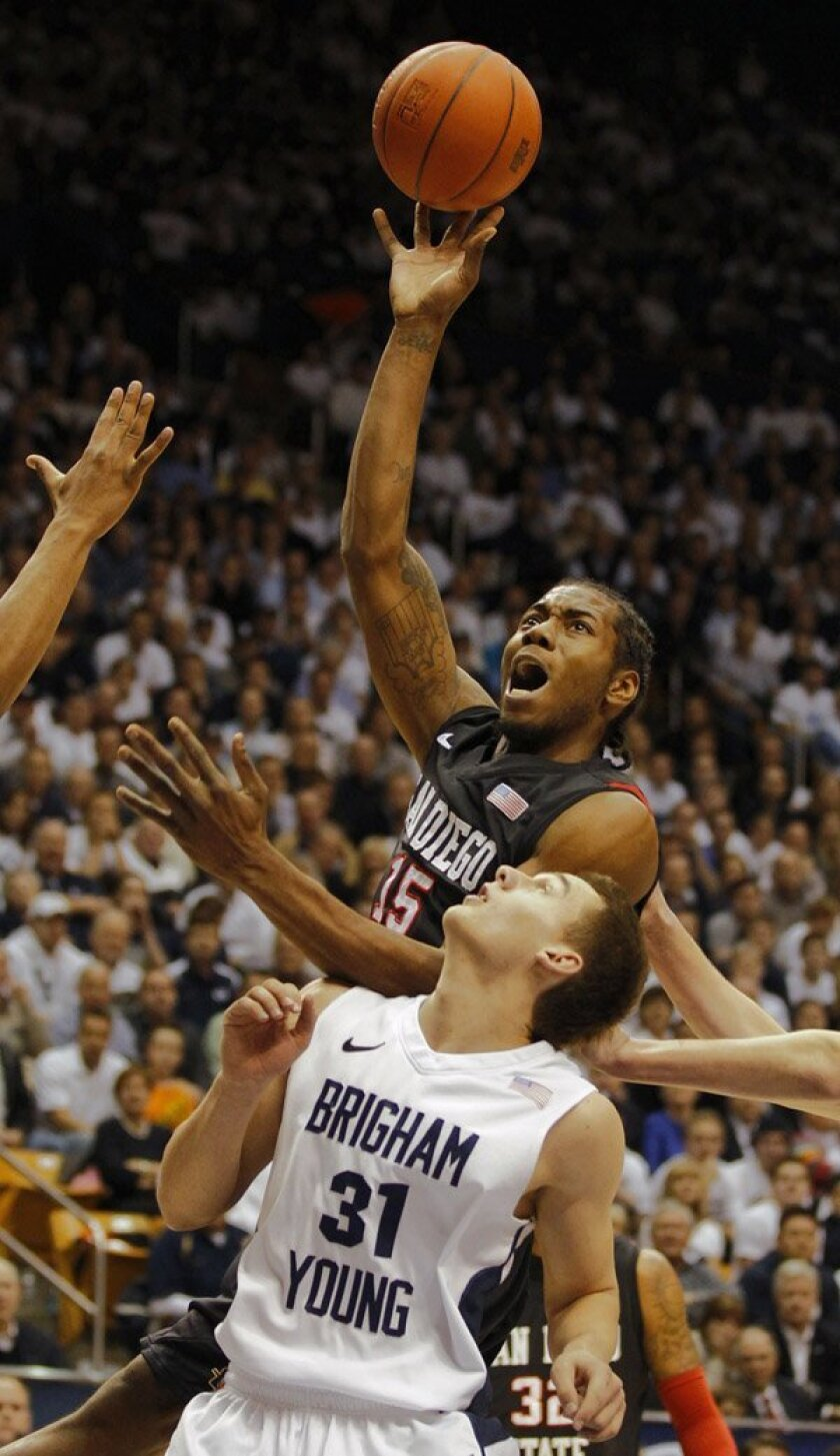 San Diego State's Kawhi Leonard, top, shoots over BYU's Kyle Collinsworth during the first half.