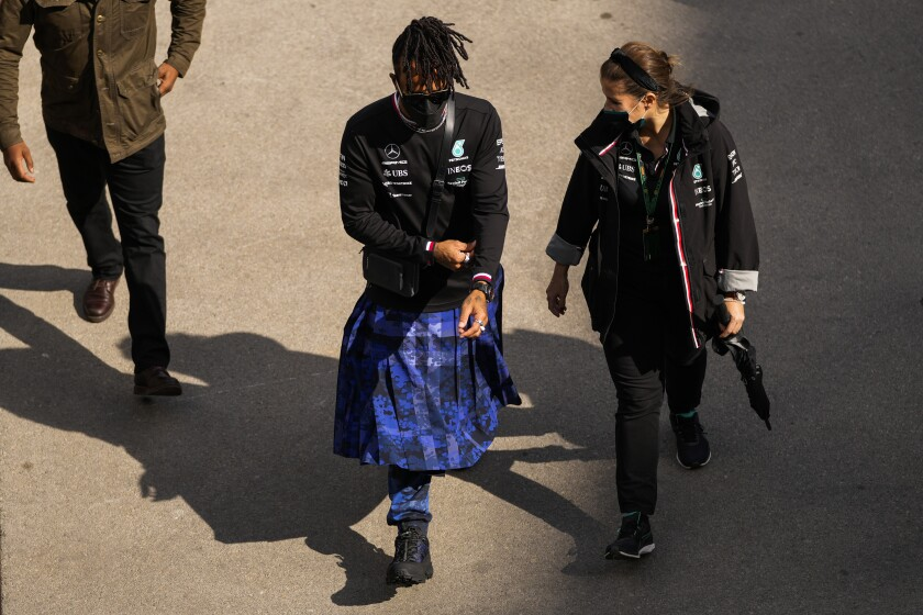 Mercedes driver Lewis Hamilton, left, of Britain walks at the paddock ahead of Sunday's Formula One Turkish Grand Prix at the Intercity Istanbul Park track, outside Istanbul, Turkey, Thursday, Oct. 7, 2021. (AP Photo/Francisco Seco)