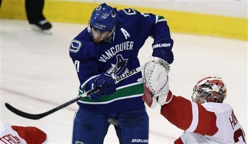 Vancouver Canucks' Ryan Kesler, left, tries to tip the puck as Detroit Red Wings' Jimmy Howard reaches to make the save during the second period of an NHL hockey game in Vancouver, B.C., Saturday, Jan. 8, 2011. (AP Photo/The Canadian Press, Darryl Dyck)