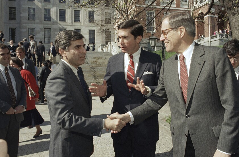 """FILE - In this April 27, 1987, file photo, Massachusetts Governor Michael Dukakis, left, shakes the hands of former Delaware Governor Pierre Du Pont, right as former Virginia Governor Charles S. Robb looks on, after both men attended the Jobs for Bay State Grads program in Boston. Pierre S. """"Pete"""" du Pont IV, a former Delaware governor and congressman who sought the 1988 Republican presidential nomination, has died at age 86. Du Pont, a scion of the family that established the DuPont Co., died at his home in Wilmington, Del., on Saturday, May 8, 2021, after a long illness, his former chief of staff, Bob Perkins, said. (AP Photo/Jim Shea, File)"""