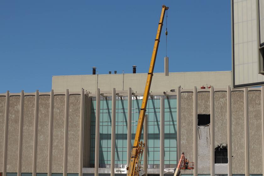 A bright yellow construction crane hoists a vertical piece of column from LACMA's facade into the air.