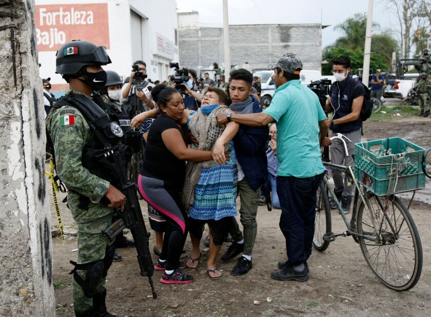 A woman receives assistance near the rehabilitation facility where 26 people were killed in Irapuato, Mexico.