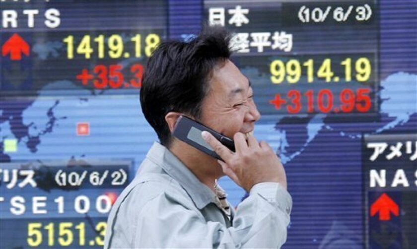 A man talks on a mobile phone in front of the electronic stock board of a securities firm in Tokyo, Thursday, June 3, 2010. Japan's benchmark Nikkei 225 stock index surged 310.95 points to 9,914. 19 Thursday, as Asian markets jumped after gains on Wall Street triggered by strong housing figures gave investors enough confidence to snap up riskier assets like shares following a monthlong slide. (AP Photo/Koji Sasahara)