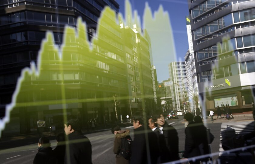 Pedestrians are reflected on an electronic stock board at a securities firm in Tokyo, Friday, Jan. 22, 2016. Asian stocks rallied Friday, extending a global market rebound fueled by the prospect of more stimulus from European policymakers and a bounce in oil prices. (AP Photo/Eugene Hoshiko)