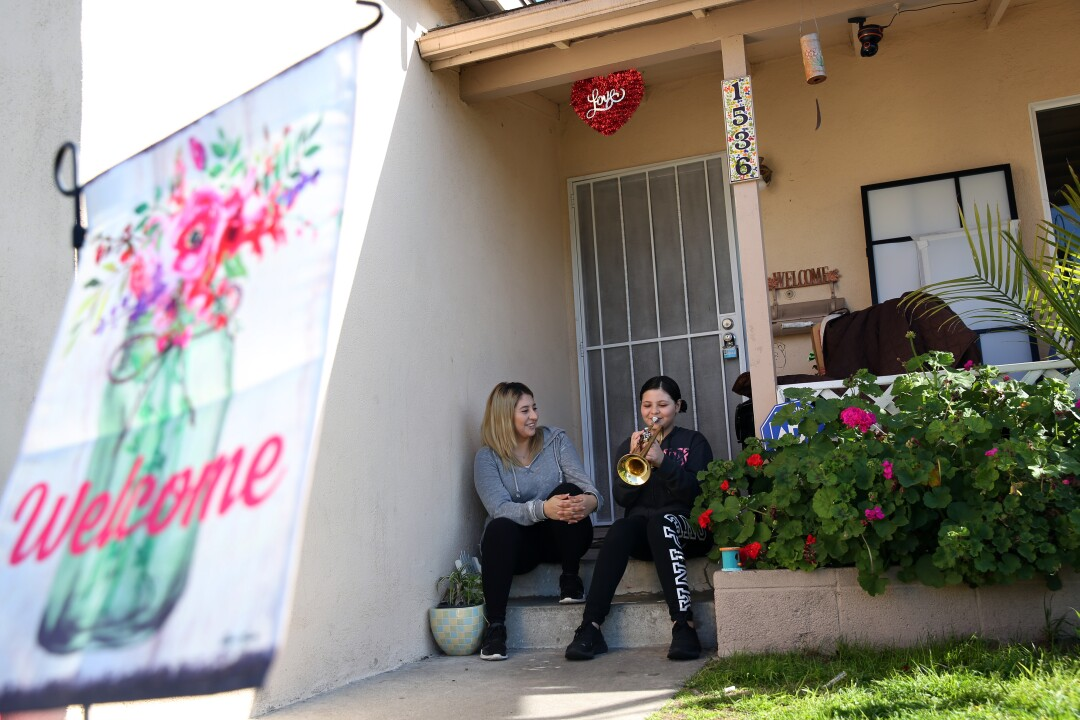 Marlene Diaz listens as her daughter Kayla plays the trumpet sitting on the stoop at their home in Torrance