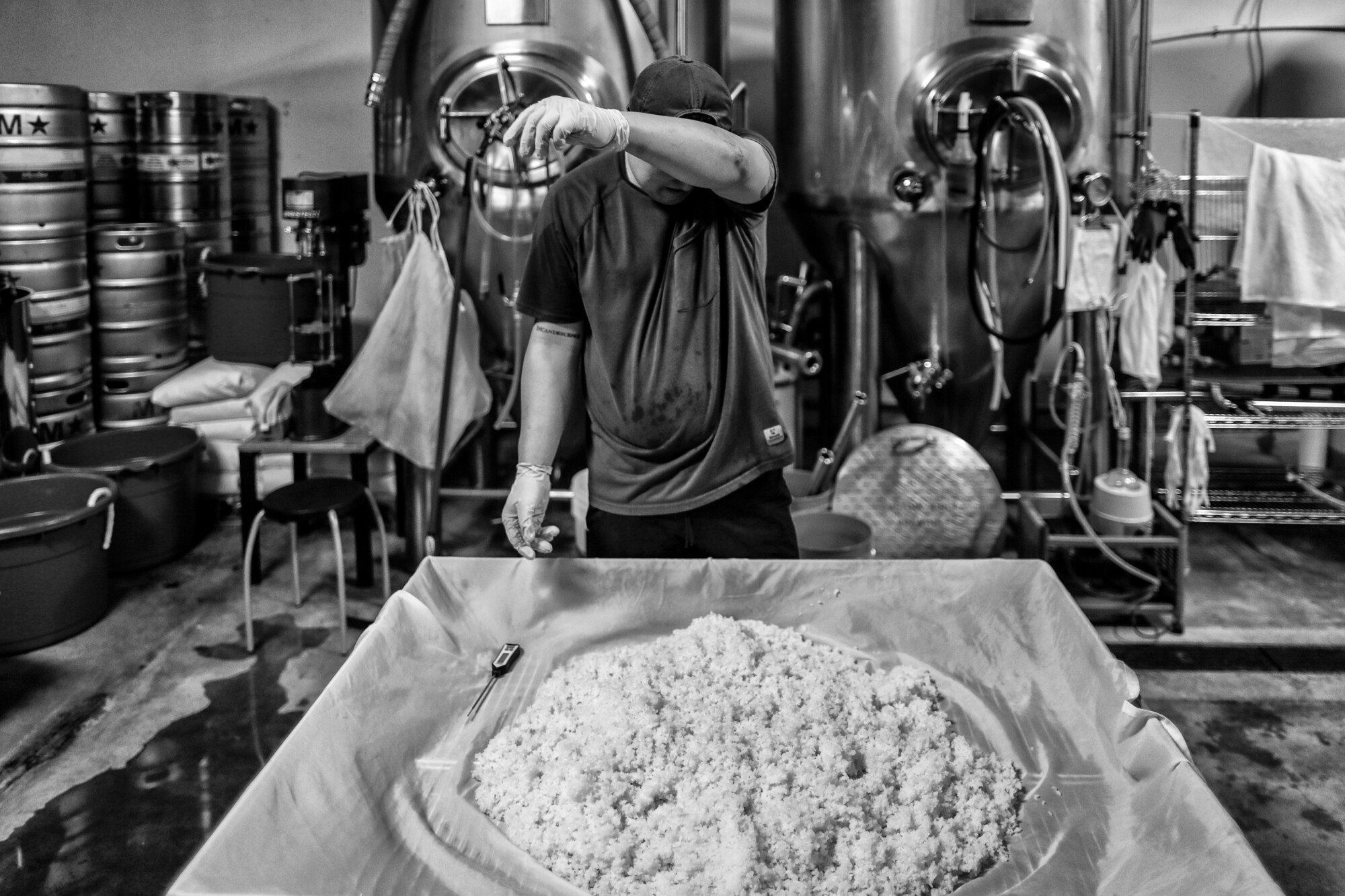 James Jin wipes sweat from his brow as he manually mixes steamed rice early in the process of brewing his craft sake.