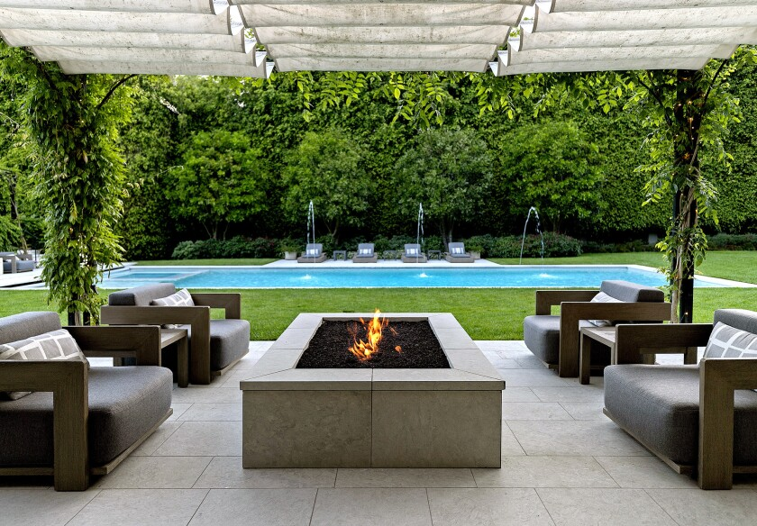 Verdant landscaping creates a backdrop for multiple patios at the Home of the Week in Beverly Hills.