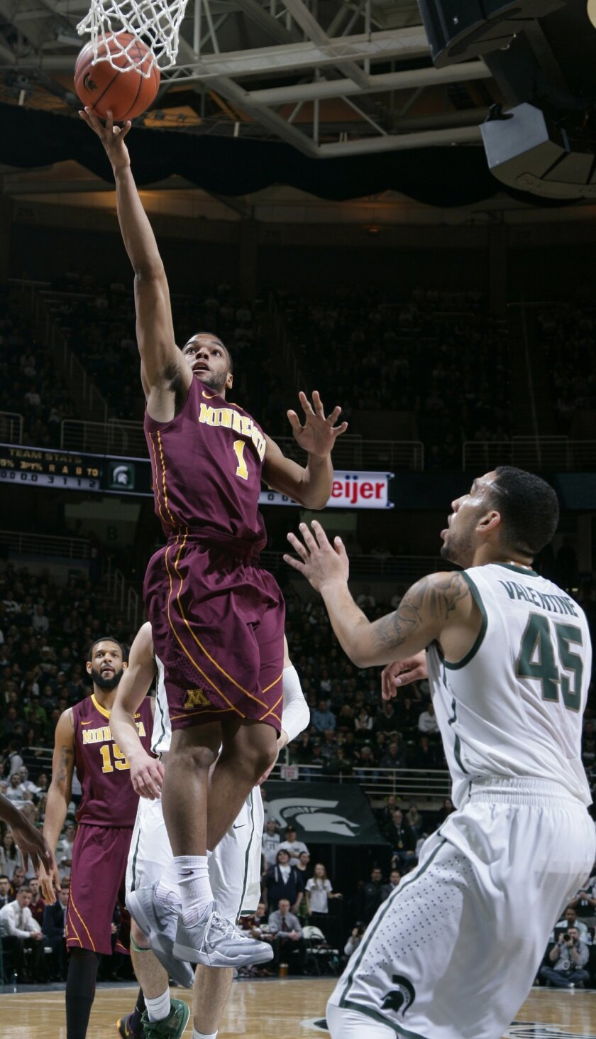 Minnesota's Andre Hollins (1) puts up a layup against Michigan State's Denzel Valentine (45) during the first half of an NCAA college basketball game, Thursday, Feb. 26, 2015, in East Lansing, Mich. (AP Photo/Al Goldis)