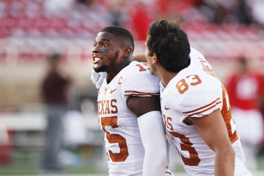 Texas defensive back Chris Brown and wide receiver Kai Money celebrate their win over Texas Tech after an NCAA college football game against Texas Tech, Saturday Sept. 26, 2020, in Lubbock, Texas. (AP Photo/Mark Rogers)