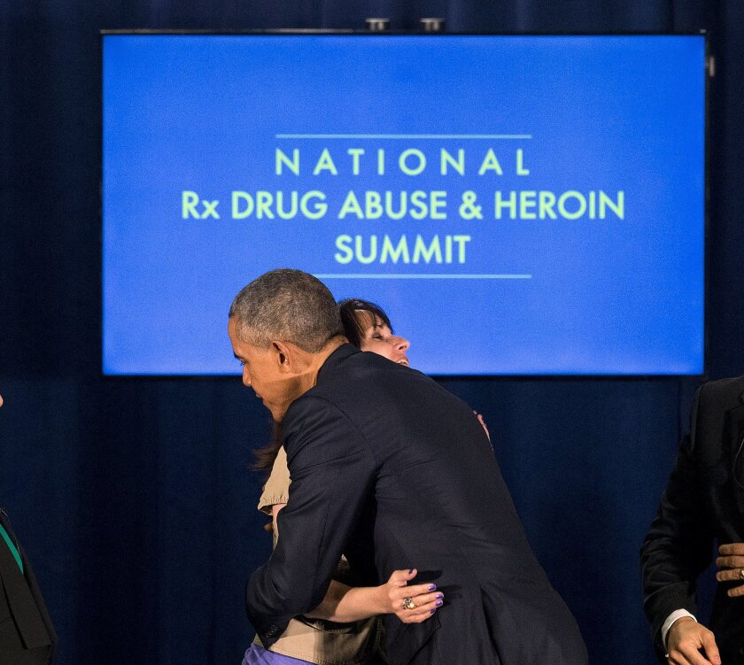 President Barack Obama hugs Crystal Oertle after a panel discussion at the National Rx Drug Abuse and Heroin Summit Tuesday, March 29, 2016, in Atlanta. Oertle spoke about her struggle with prescription drug addiction. (AP Photo/John Bazemore)