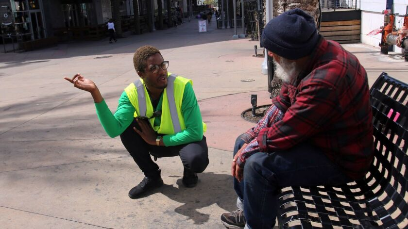 La Quentan McGuire, Ambassador Team Leader, talks with a homeless man and guides him to facilities t