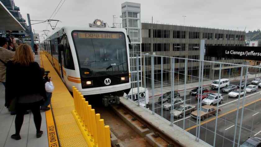 A Metro Expo light rail cars pulls into La Cienega/Jefferson station while traffic down below plods along during morning rush hour.
