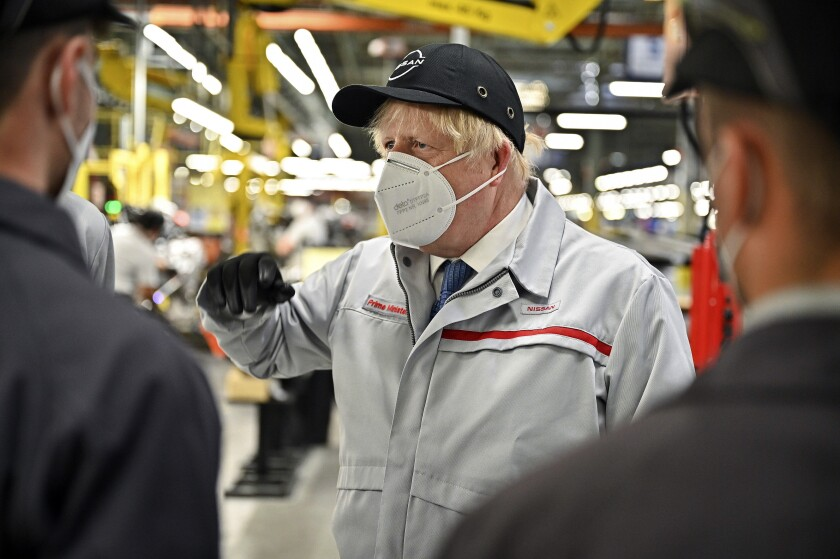 """Britain's Prime Minister Boris Johnson during his visit to Nissan plant in Sunderland, England, Thursday July 1, 2021. Johnson said unspecified """"extra precautions"""" will be needed in coming weeks even as he voiced confidence Thursday that the remaining restrictions on social contact in England will be lifted on July 19. During a visit to the Nissan car plant in the north England city of Sunderland, Johnson said he is planning to reveal details of what the end of lockdown restrictions will look like in the coming days. (Jeff J Mitchell/Pool Photo via AP)"""