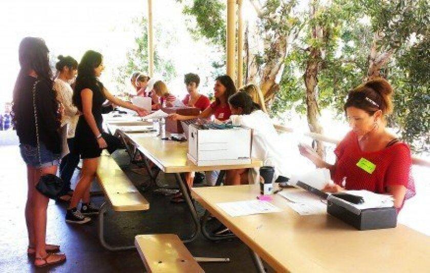 Parent volunteers help students with paper work.
