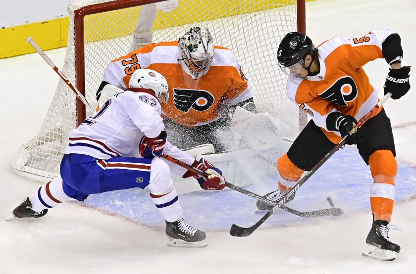 Philadelphia Flyers goaltender Carter Hart (79) makes a save on Montreal Canadiens' Artturi Lehkonen (62) as Flyers' Philippe Myers (5) defends during the second period of an NHL Eastern Conference Stanley Cup hockey playoff game in Toronto, Wednesday, Aug. 12, 2020. (Frank Gunn/The Canadian Press via AP)