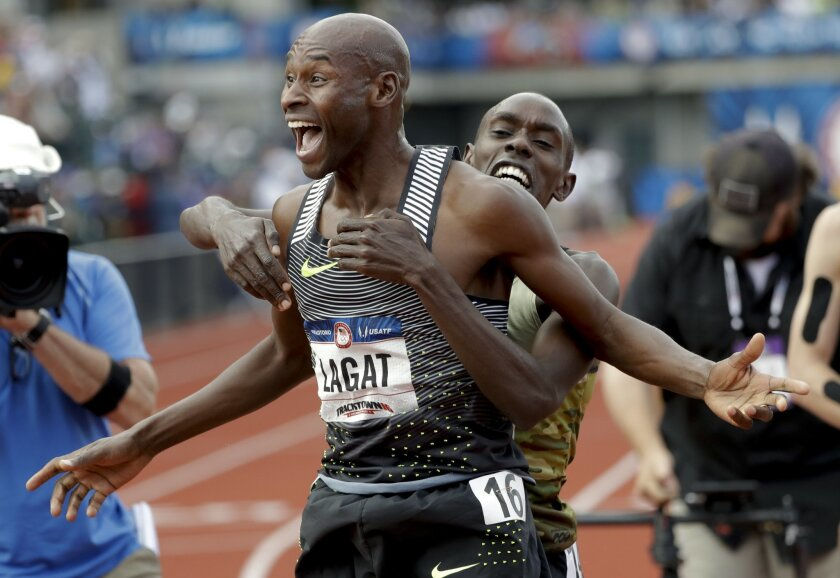 Bernard Lagat, left, celebrates his win in the finals of the men's 5000-meter run with Paul Chelimo at the U.S. Olympic Track and Field Trials, Saturday, July 9, 2016, in Eugene Ore. (AP Photo/Marcio Jose Sanchez)